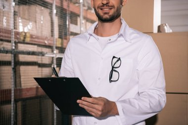 partial view of smiling storekeeper holding clipboard in warehouse