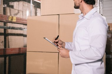 cropped view of storekeeper in white coat writing on clipboard in warehouse