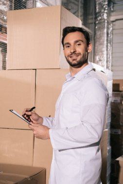 Handsome storekeeper in white coat smiling at camera while writing on clipboard in warehouse stock vector
