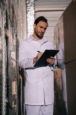 focused storekeeper in white coat writing on clipboard in warehouse