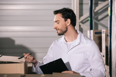 handsome storekeeper inspecting cardboard boxes while holding clipboard and pen