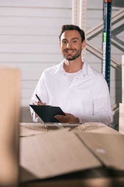 selective focus of smiling storekeeper holding clipboard while standing near cardboard boxes