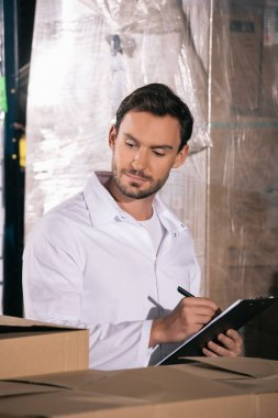 concentrated storekeeper writing on clipboard while looking at packages in warehouse