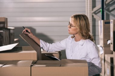 focused storekeeper in white coat inspecting cardboard boxes in warehouse