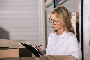 concentrated storekeeper in glasses writing on clipboard in warehouse