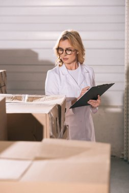selective focus of storekeeper writing on clipboard while looking at cardboard boxes