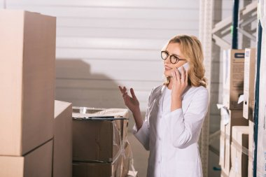 smiling storekeeper talking on smartphone and showing question gesture while looking at cardboard boxes in warehouse