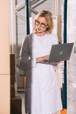 focused storekeeper using laptop while looking at cardboard boxes in warehouse