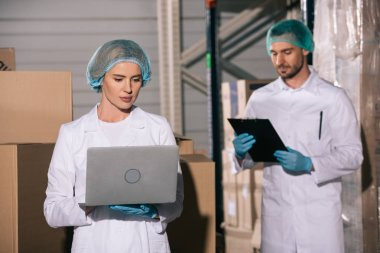 attractive storekeeper using laptop near colleague looking at clipboard in warehouse