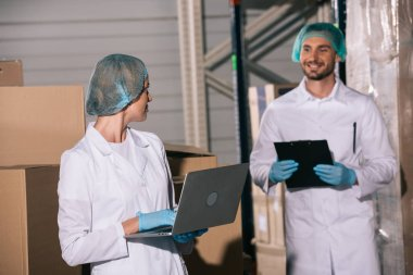smiling storekeeper holding clipboard and looking at colleague using laptop in warehouse