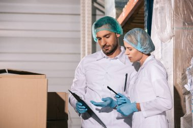two storekeepers in white coats and hairnets looking at clipboard in warehouse