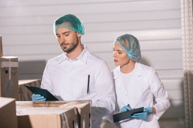attractive storekeeper looking at clipboard in hands of handsome colleague while standing near cardboard boxes