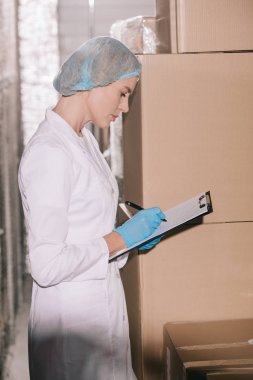 focused storekeeper in hairnet writing on clipboard while standing near carton boxes in warehouse