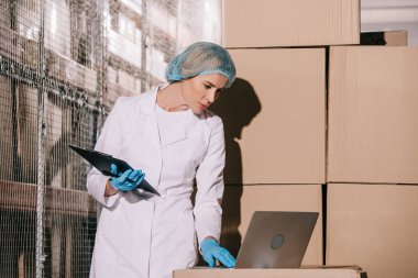 concentrated storekeeper in white coat and hairnet using laptop and holding clipboard