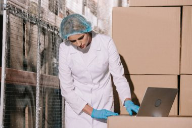Concentrated storekeeper in white coat and hairnet using laptop while inspecting packages in warehouse stock vector