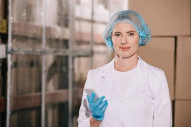 attractive storekeeper in hairnet smiling at camera while holding smartphone