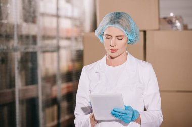 concentrated storekeeper in hairnet using digital tablet in warehouse