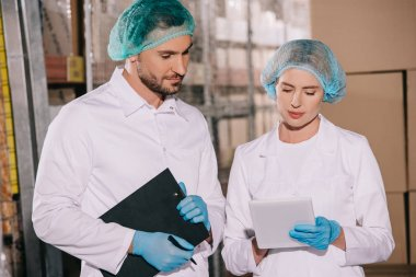 handsome storekeeper holding clipboard near attractive colleague using digital tablet