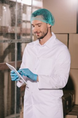 smiling storekeeper in white coat and hairnet using digital tablet in warehouse