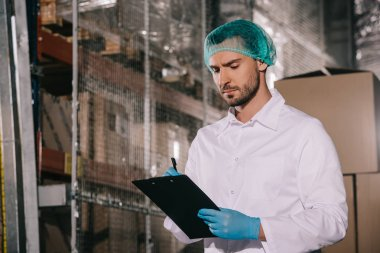 concentrated storekeeper in white coat and hairnet writing on clipboard in warehouse