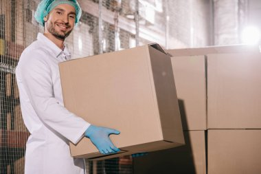 cheerful storekeeper smiling at camera while holding cardboard box in warehouse