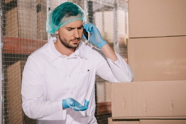 serious storekeeper talking on smartphone while standing near cardboard boxes in warehouse