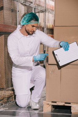 concentrated storekeeper inspecting cardboard box while holding clipboard