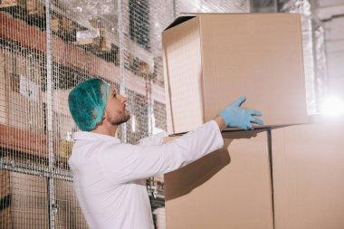 Storekeeper in white coat and hairnet taking cardboard box in warehouse stock vector