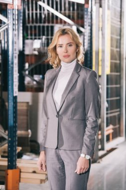 confident businesswoman in formal wear looking at camera while standing in warehouse