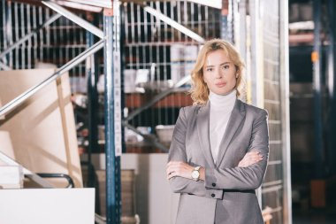 confident businesswoman looking at camera while standing in warehouse with crossed arms