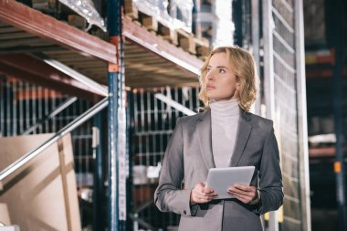 confident businesswoman holding digital tablet while looking away in warehouse