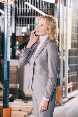 serious businesswoman talking on smartphone and looking away in warehouse