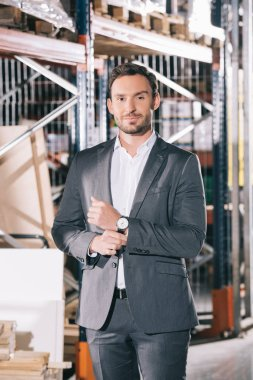 handsome businessman in formal wear smiling at camera while standing in warehouse