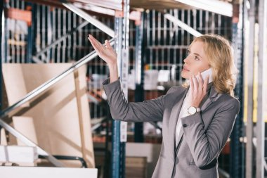 serious businesswoman talking on smartphone, looking away and pointing with hand in warehouse