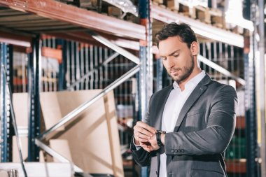 serious businessman checking time on wristwatch while standing in warehouse