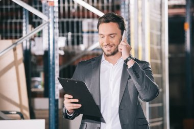smiling businessman talking on smartphone and looking on clipboard in warehouse