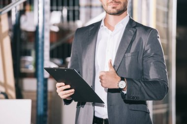 cropped view of businessman in formal wear holding clipboard in warehouse