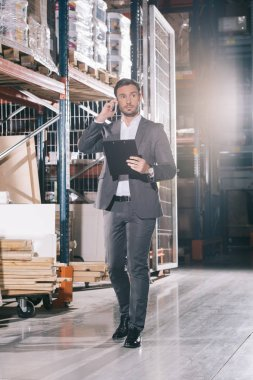 serious businessman talking on smartphone and holding clipboard in warehouse