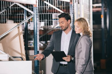 handsome businessman pointing with finger at construction materials while standing near businesswoman