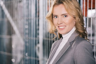 attractive businesswoman smiling at camera in warehouse