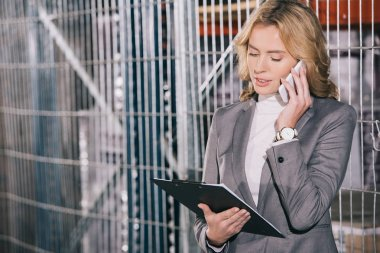 attractive businesswoman talking on smartphone and holding clipboard in warehouse