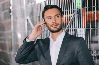confident businessman looking away while talking on smartphone in warehouse