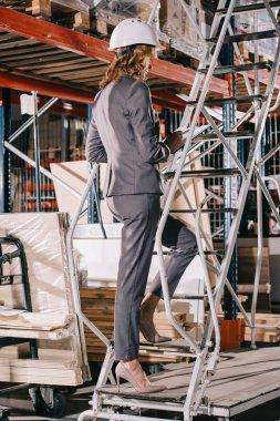 businesswoman in formal wear and helmet standing on stepladder in warehouse