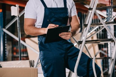 Cropped view of warehouse worker in overalls writing on clipboard in warehouse stock vector
