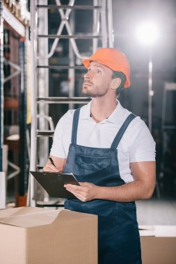 Concentrated warehouse worker looking away while writing on clipboard stock vector