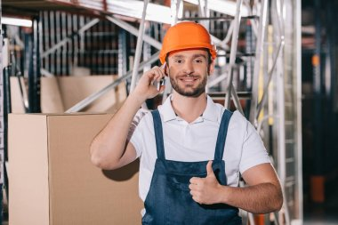 Smiling warehouse worker talking on smartphone, looking at camera and showing thumb up stock vector
