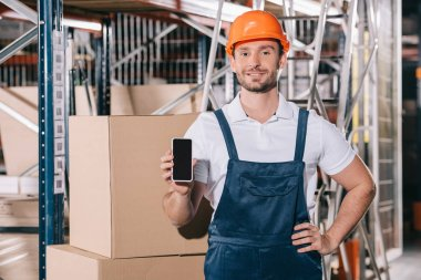 Smiling loader standing with hand on hip and showing smartphone with blank screen stock vector