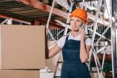 usmívající se dělnice mluví na smartphone, zatímco stojí v blízkosti lepenkových krabic
