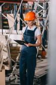 selektiver Fokus der Arbeiterin in Overalls und Helm, die in der Nähe von Baumaterialien steht und auf Klemmbrett schreibt