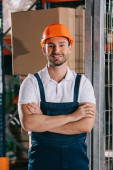 Photo handsome warehouse worker smiling at camera while standing with crossed arms